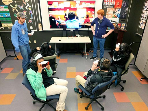 Photo of K. CAD students overseeing elementary students using the game with virtual reality headsets.